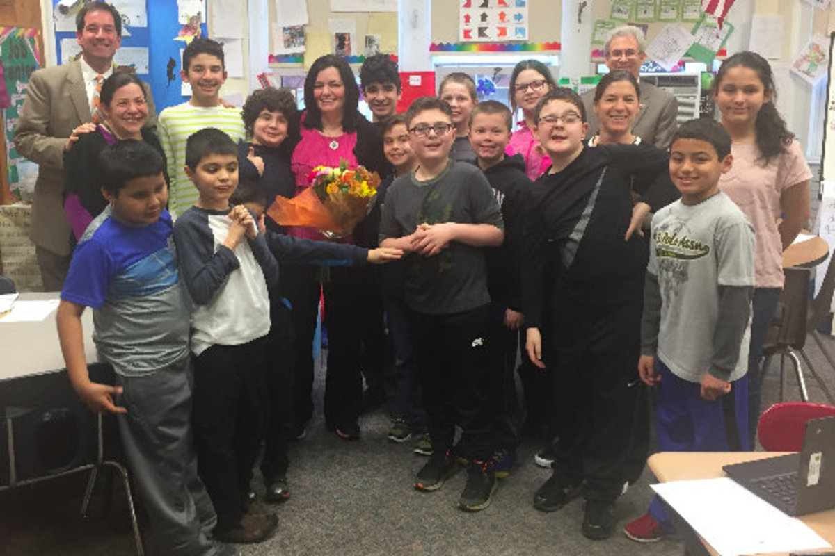 Kathy Davies is surounded by some of her students at Patrick M. Villano Elementary School. Davies started her career in the Emerson Public School district as a teaching assistant and is now a special education instructor.